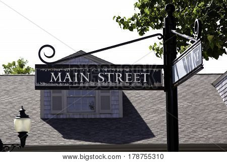 Wide close up view of a Main Street sign in Cape Cod, Massachusetts with sky and a roof as offset background on a bright and sunny day in mid September.