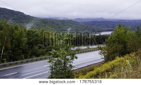 Wide view looking down at the highway below outside of Boston, Massachusetts, heavy mist hangs over the mountains saturated green landscape and lake in the distance on an overcast rainy day in mid September.