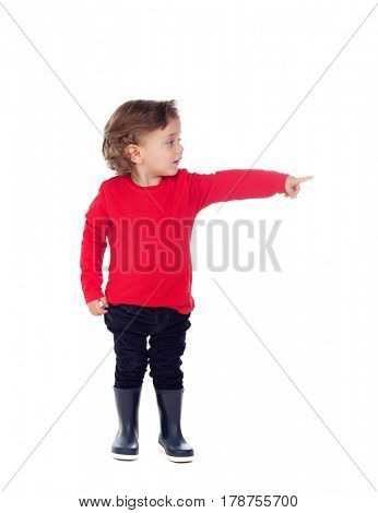 Adorable baby with red shirt pointing with his finger isolated on a white background