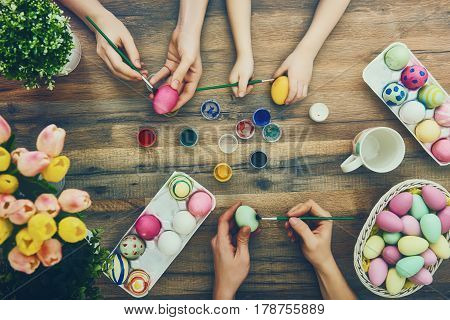 family coloring eggs for Easter on a wooden table. Mother, father and child bonding.
