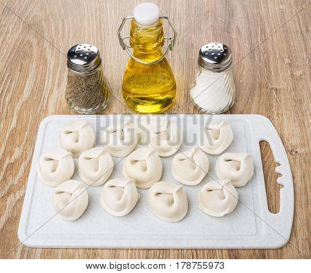 Raw Dumplings On Cutting Board, Pepper, Salt And Vegetable Oil