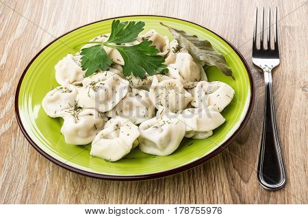 Boiled Dumplings With Parsley And Dill In Plate, Fork