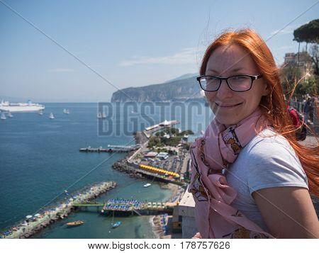 Red hair Girl in glasses traveling in Europe Italy - sorrento, telephoto