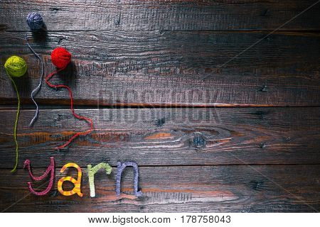 Knit shop background with text 'Yarn' of handmade colorful letters. Rustic wood board field