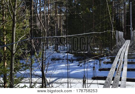 Old cracked wood suspension bridge for pedestrian over a partly frozen river picture from the North of Sweden.