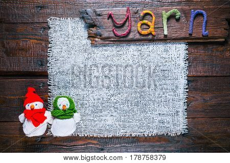 Knit shop background with title wood sign 'Yarn' of handmade letters and couple of handmade snowmen of yarn skeins