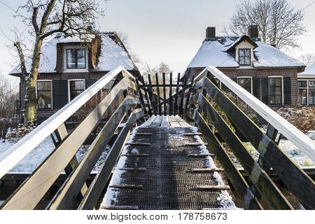 Giethoorn The Netherlands - January 18 2016: Winterlandscape with canal farmhouses and bridge in the typical dutch village of Giethoorn in the province of Overijssel in the Netherlands.