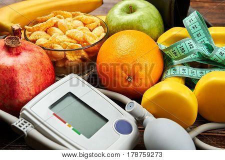 Tonometer, apple, dumbbells and orange. Spend life healthy.