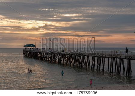 Evening view of jetty and bathers on South Australian coast.
