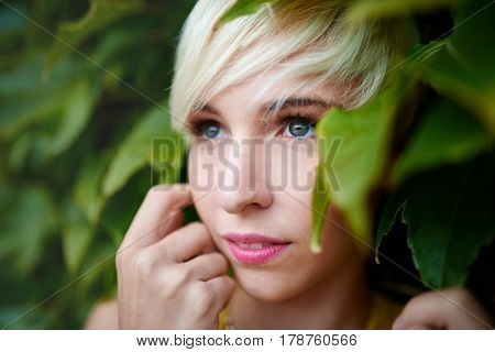 Portrait of an urban boyish blonde millennial girl looking cute, shy and being flirty in front of a leafy background.