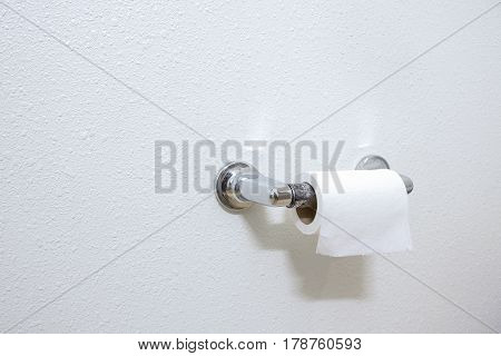 A Roll Of White Toilet Paper Hanging On A Chrome Toilet Roll Holder