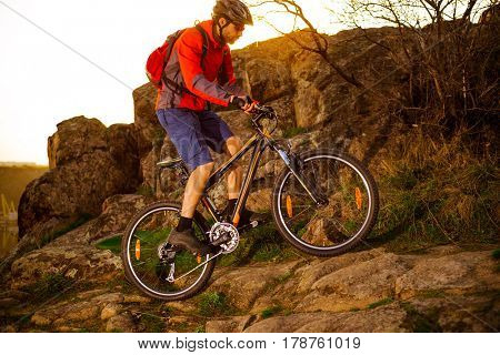 Cyclist Riding the Mountain Bike Up Rocky Hill on the Spring Trail at Sunset. Extreme Sports Concept.