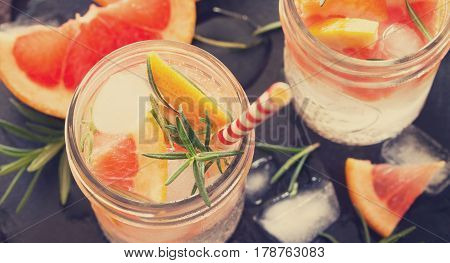 Refreshing Summer Drink With Ice With Rosemary And Grapefruit On A Stone Background. The Concept Of