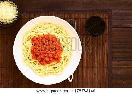 Traditional Italian Spaghetti alla Marinara (spaghetti with tomato sauce) in bowl with red wine and grated cheese on the side photographed overhead on dark wood with natural light