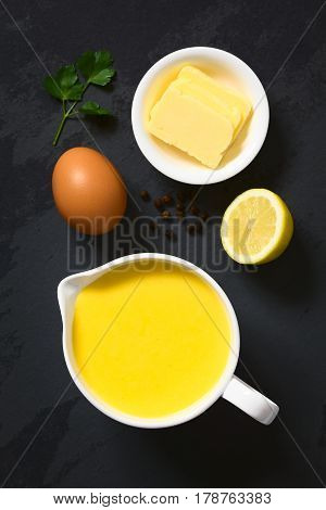 Hollandaise sauce a basic sauce of the French cuisine served in a sauce boat with ingredients (egg butter lemon pepper) on the side photographed overhead on slate with natural light