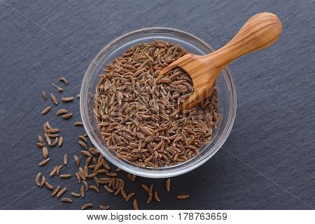 seeds of cumin, caraway in a bowl and wooden scoop on black