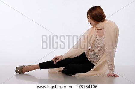 Dark-haired girl sits in a beige shawl on a light backdrop. She looks to the side, scarf wrapped around her neck and shoulders. Her hands are on the floor and leg. Emotion: tenderness, dreaminess.