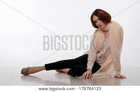 Dark-haired girl sits in a beige shawl on a light backdrop. She looking, bowing her head, scarf wrapped around her neck and shoulders. Her hands on the floor. Emotion: tenderness, dreaminess.