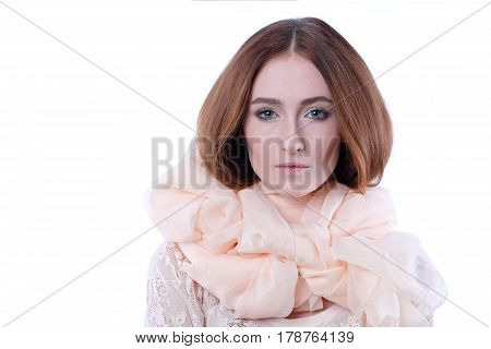 Young girl in elegant beige scarf around her neck on white backdrop. Red-haired woman looks at the camera. Huge creme schawl. Isolated shot. Skin texture. Romance, theater. Emotion: lovely, tenderness