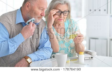Portrait of an elderly couple with pills