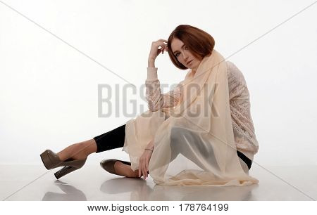 Young girl in big shawl sits on the floor. Her legs bent at the knees, hand touching a forehead. Black skinny pants, heels, creme scarf, fashion, make-up.