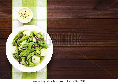 Green bean potato and red onion salad with parsley hollandaise sauce on the side photographed overhead on dark wood with natural light