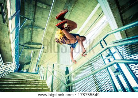 young man practicing parkour jumping on stairs with metal fence, city extreme sport concept shot from below