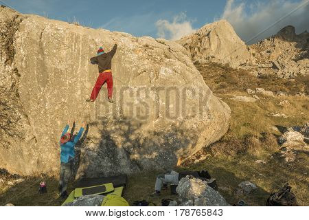 Back view of people climbing rock boulder in sunset. Roao Villanueva del Rosario Malaga