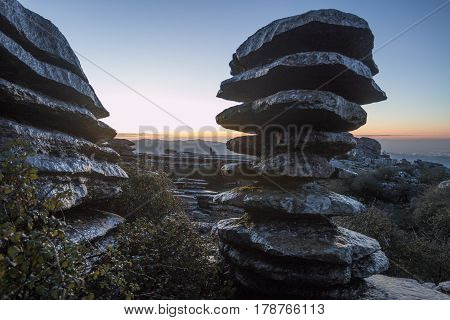 The Tornillo in Torcal Antequera Malaga. Plain big stones lying in towers on background of sunset in mountains