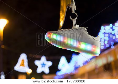Close up shot of glowing sportive shoe hanging on blurred background of lights in dark