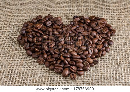 Heart of coffee beans with hearts on sackcloth.