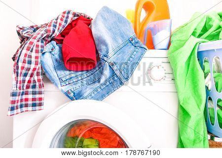 Messy laundry clothes on washing machine room at home - Colorful clothing on top and inside washer with detergent powder and bottles - Concept of housework and energy expense -