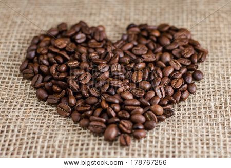 Coffee beans laid out in the heart. Shallow depth of field.