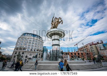 Statue of warrior on a horse in Skopje. Skopje, Macedonia September 22, 2016: Wide angle view of statue of warrior on horse at public square in center of Skopje Macedonia. Ordinary people walking around on the square near the statue.