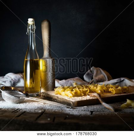 Pasta, olive oil on a wooden table. Dark background.