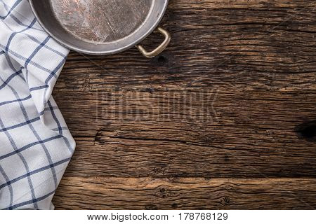 Top view of checkered tablecloth or napkin on empty wooden table.Metal old retro empty pan on oak kitchen table. Top view.