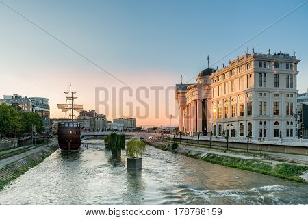 Wide view of the center of skopje Macedonia with the river Vardar, ship and surrounding buildings, late afternoon with sunset.