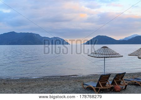 Sunbeds on marmaris beach with mountain views.