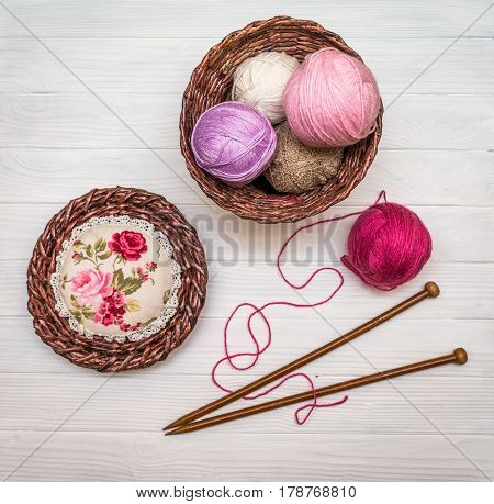 From above the colored balls of yarn in wicker basket with needles on white wooden board in Ukraine