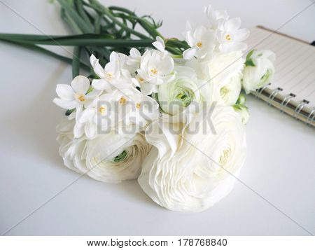 Spring styled stock photo. Still life with daffodils and Persian buttercup flowers, Narcissus, Ranunculus and notebook. Blurred background, image for blog or social media.