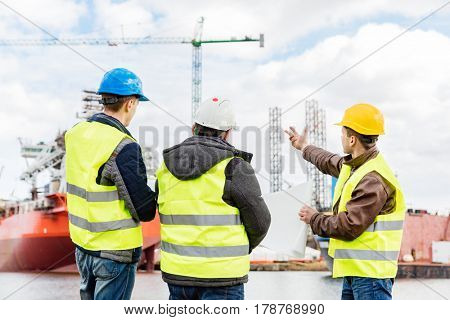 Senior engineer builder at the construction site in a port. Wearing safety helmet and yellow vest. Shipbuilding industry.
