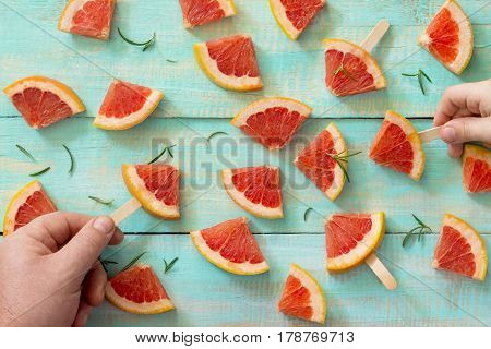 Sliced Red Grapefruit Ice Cream With Rosemary On The Background Of Old Wooden. The Concept Of A Heal
