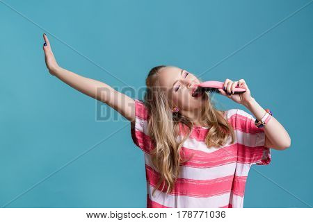 young funny blond woman sings using pink hairbrush  on a blue background