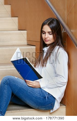 Portrait of Caucasian brunette young girl woman student in white shirt and blue jeans holding reading notes in exercise book sitting on staircase preparing for exams