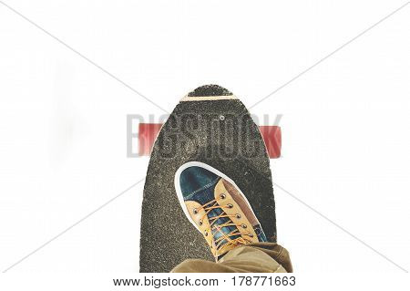 Detail skateboard partially large with the legs of a man in sneakers