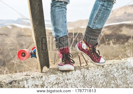 Close-up of female legs in jeans and sneakers next to a longboard or skateboard