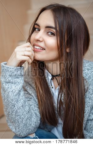 Closeup portrait of smiling Caucasian brunette young beautiful girl woman with long dark hair and brown eyes in white shirt and grey coat sitting on staircase looking in camera