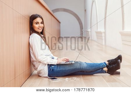 Portrait of beautiful white Caucasian brunette young girl woman model with long dark hair in white shirt and blue jeans sitting on floor in hall at college university working on laptop