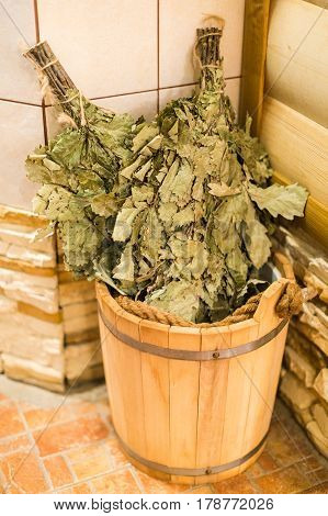 Bath accessories in traditional Russian sauna. Bath brooms from oak in wooden sauna bucket in the russian bath close up. Oak venik for banya.