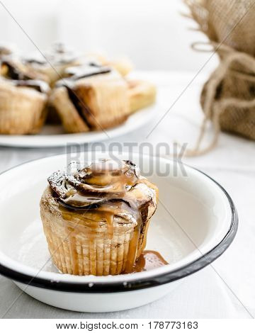Bun with apple and caramel in a white plate on a light background. Selective focus
